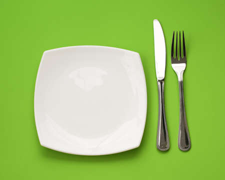 dinner plate: Knife, square white plate and fork on green background Stock Photo