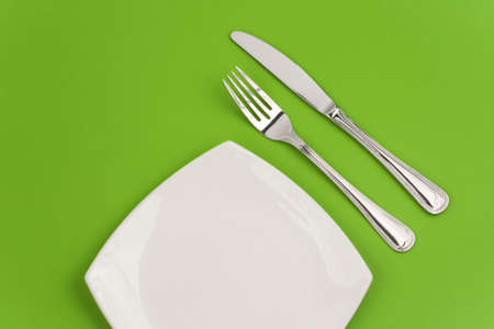 Knife, square white plate and fork on green background Stock Photo - 6021325