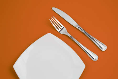 Knife, square white plate and fork on orange background Stock Photo - 6021328
