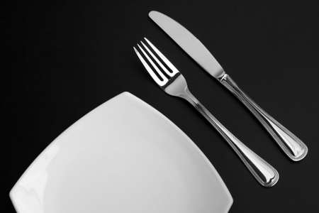 Knife, square white plate and fork on black background Stock Photo - 6021333