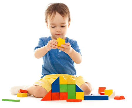 block: Cute little boy is playing with colorful building wooden blocks Stock Photo