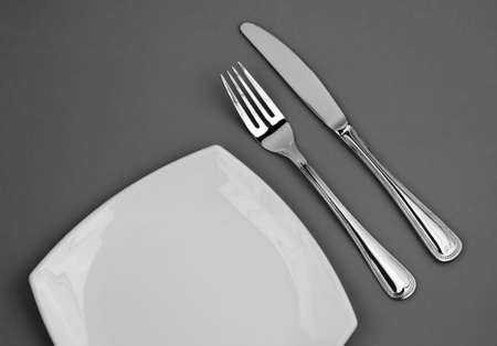 Knife, square white plate and fork on gray background Stock Photo - 6069249