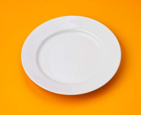 White round plate on orange background photo