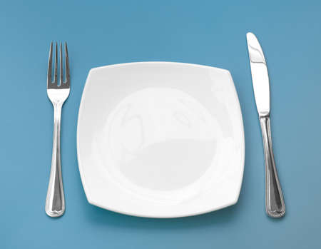 Knife, square white plate and fork on blue background Stock Photo - 6197658