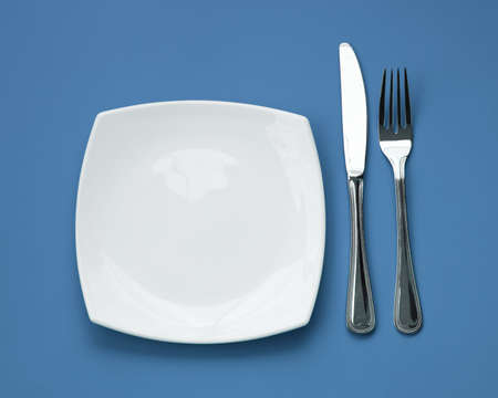 Knife, square white plate and fork on blue background Stock Photo - 6239946