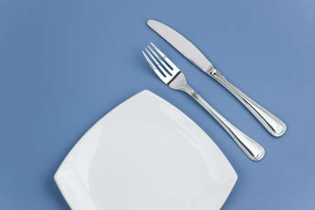 Knife, square white plate and fork on blue background photo