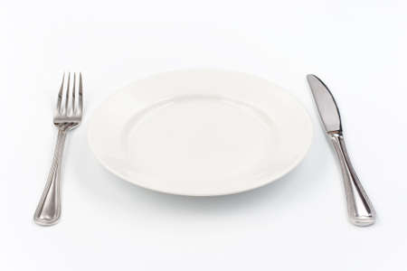 Place setting for one person. Knife, white plate and fork. photo