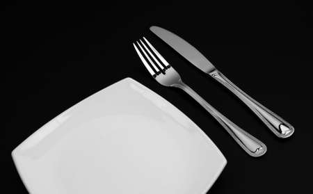 Knife, square white plate and fork on black background Stock Photo - 6344029
