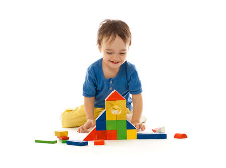 Cute little boy is playing with colorful building wooden blocks isolated on white photo