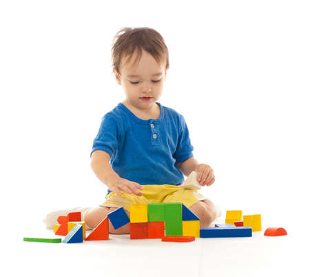 Cute little boy is playing with colorful building wooden blocks photo