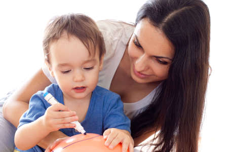 Mother and son drawing picture on red balloon together photo