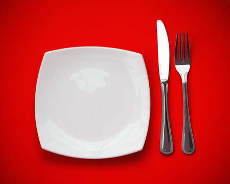 Knife, square white plate and fork on red background Stock Photo - 6790793