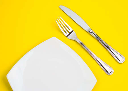 Knife, square white plate and fork on yellow background photo