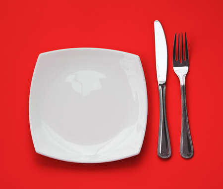 Knife, square white plate and fork on red background Stock Photo - 6790805