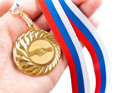 Golden medal with handshake symbol on palm Stock Photo - 6912673