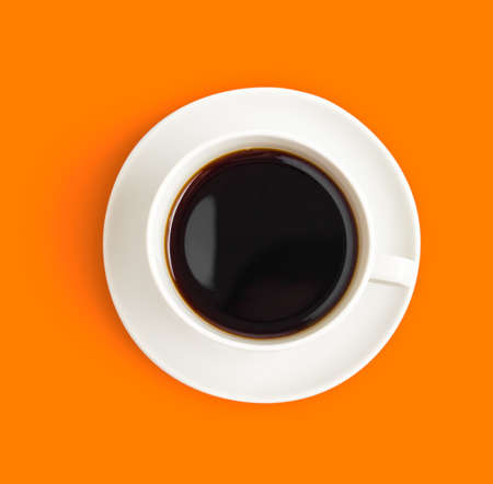 Top view of black coffee cup on orange background photo