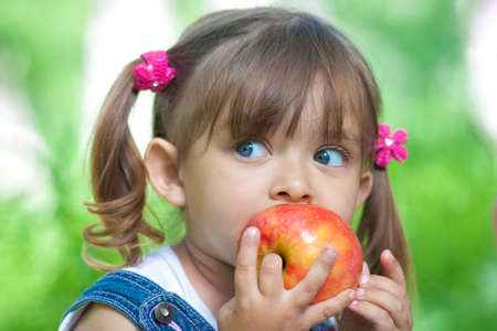 Little girl portrait eating red apple outdoor Stock Photo - 7307478