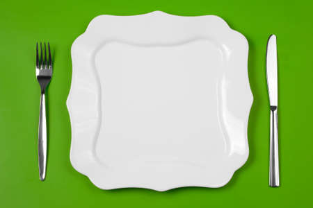 Knife, figured white plate and fork on green background Stock Photo - 7422338