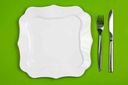 Knife, figured white plate and fork on green background Stock Photo - 7422336