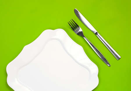 Knife, figured white plate and fork on green background Stock Photo - 7422337