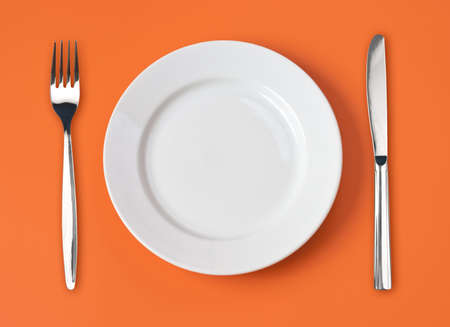 Knife, white plate and fork on orange background Stock Photo - 7422349