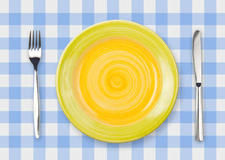 Knife, yellow plate and fork on yellow checked tablecloth photo