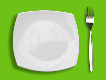 square white plate and fork on green background photo