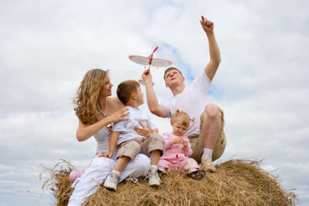 Happy family launching toy aircraft model sitting on haystack together photo