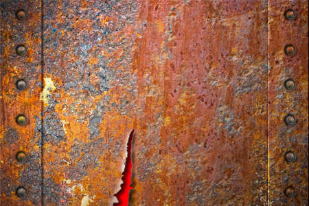 Torn rusty metal texture with rivets over red background Stock Photo - 7526681