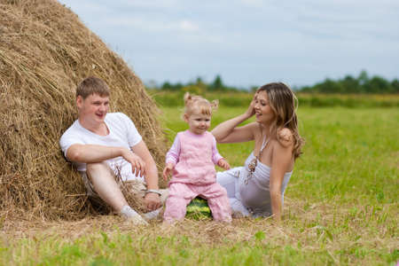 Happy family in haystack or hayrick with watermelon Stock Photo - 7526700