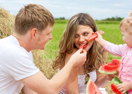 Happy family in haystack feeding mother with watermelon photo