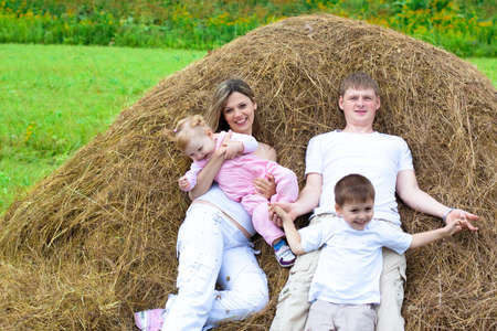 Happy family has fun in haystack together Stock Photo - 7873023