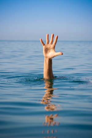single hand of drowning man in sea asking for help Stock Photo - 7880320
