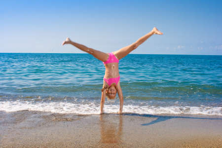 schoolgirl making gymnastics on seashore photo