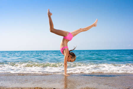 schoolgirl making gymnastics on seashore Stock Photo - 7873018