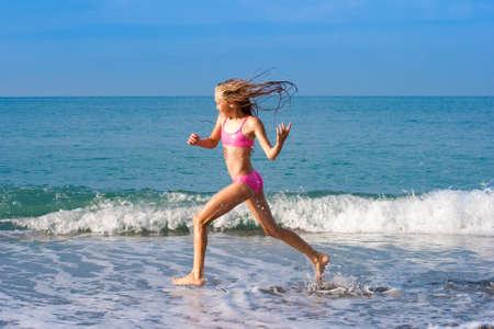 schoolgirl running on seashore photo