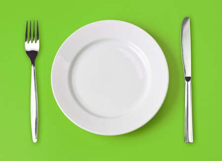 Knife, white plate and fork on green background photo