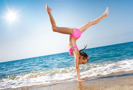 schoolgirl making gymnastics on seashore photo