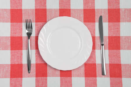Knife, white plate and fork on red checked tablecloth photo