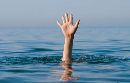 drown: single hand of drowning man in sea asking for help