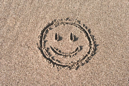Smiley face drawn on bach sand photo