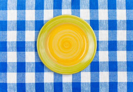 Round yellow plate on checked tablecloth photo