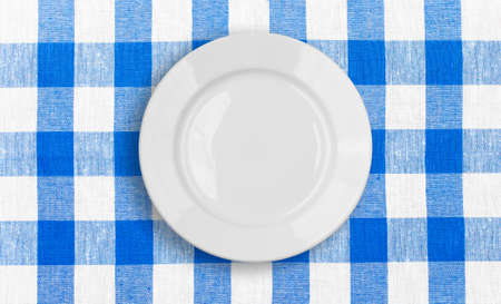 white plate on blue checked fabric tablecloth photo