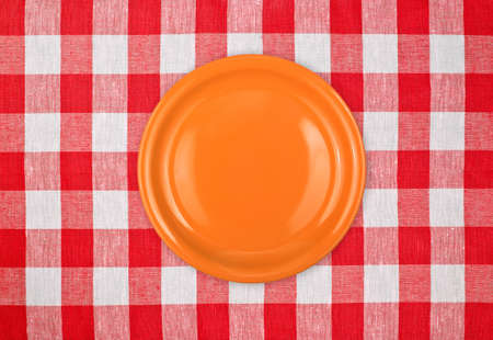 orange plate on red checked tablecloth photo