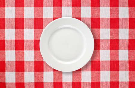 piastra bianca sulla tovaglia checked rosso