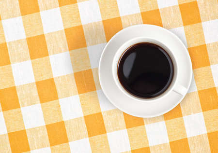 Top view of black coffee cup on checked tablecloth photo