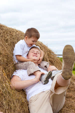 Father and son playing in haystack together Stock Photo - 8261007