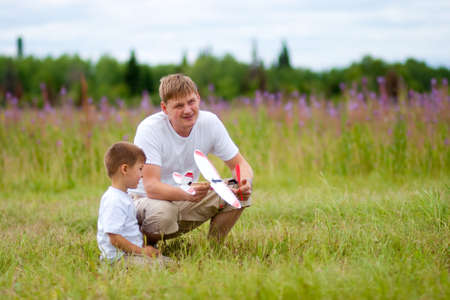 Father and son launch plane model in summer field photo