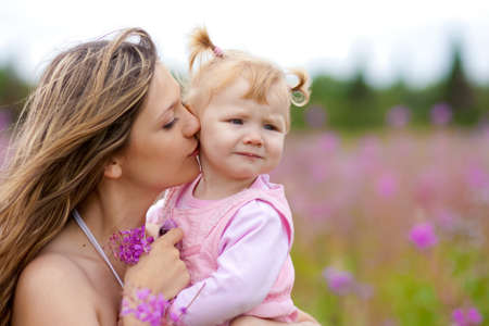 Mother kissing daughter in meadow outdoor photo