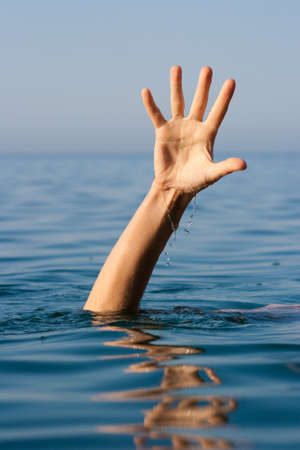single hand of drowning man in sea asking for help Stock Photo - 8261010
